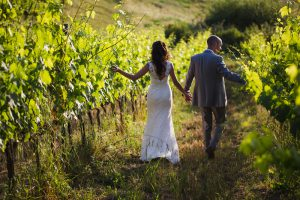 walking through the vineyards in Tuscany when to have Wedding in Italy