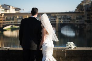 just married in Italy couple looking at ponte vecchio in florence