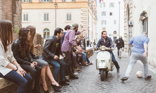 about us driving a vespa while playing soccer to offer the best tours in Rome